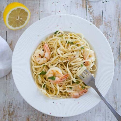 Shrimp Scampi Linguine served on a table with a lemon on the side