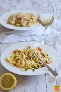 Shrimp Scampi Linguine served in white plates with a glass of wine and a lemon on a side