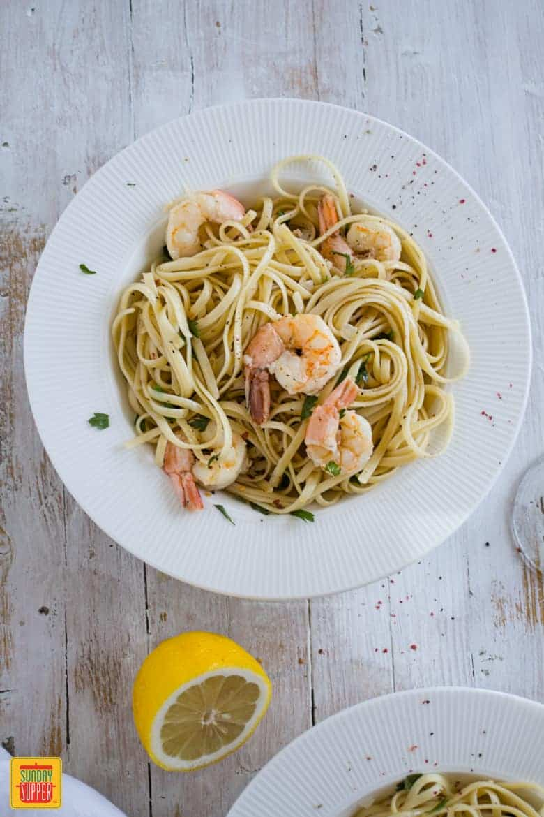 Shrimp Scampi Linguine served in a plate on a rustic wooden table