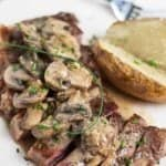 Steak diane recipe sliced on a white plate next to a baked potato cut in half