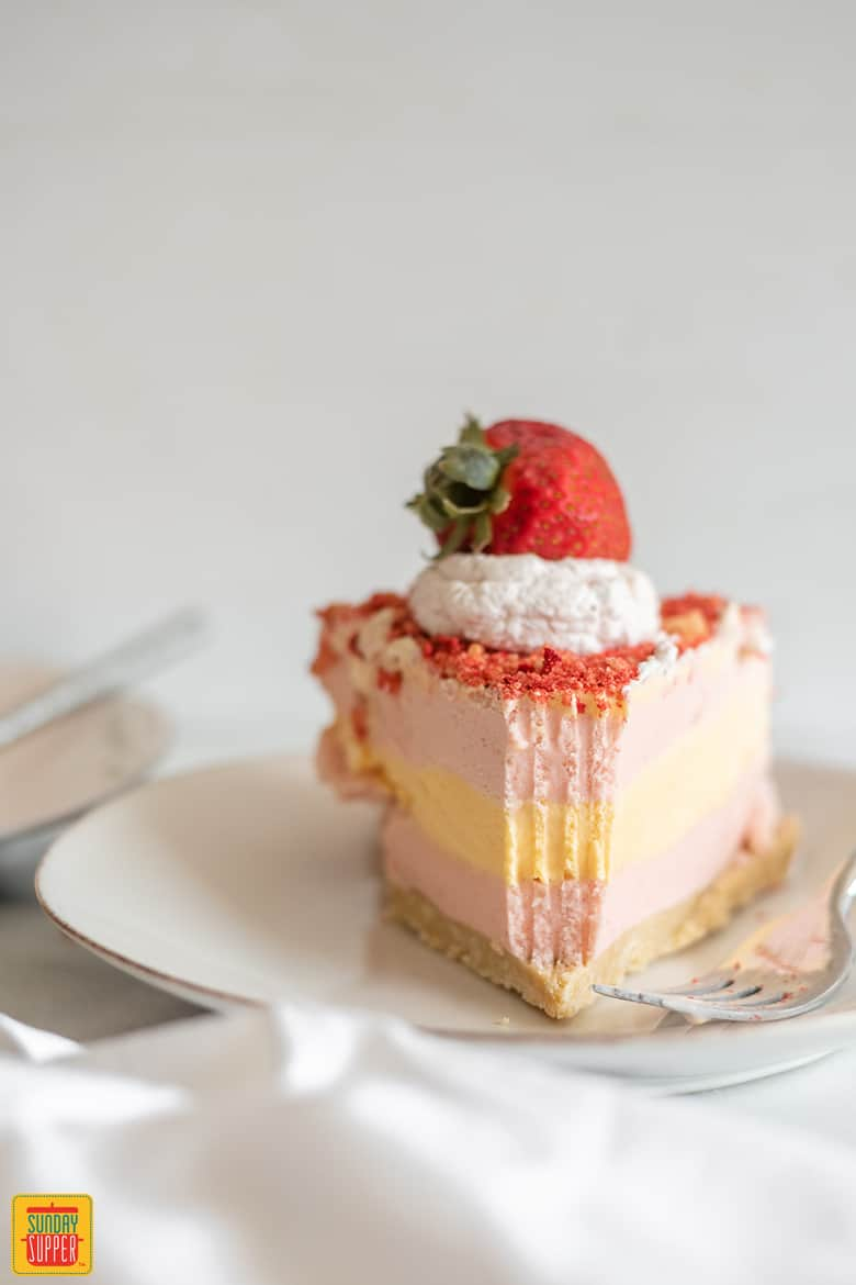 A bite taking out of strawberry shortcake ice cream cake with a fork
