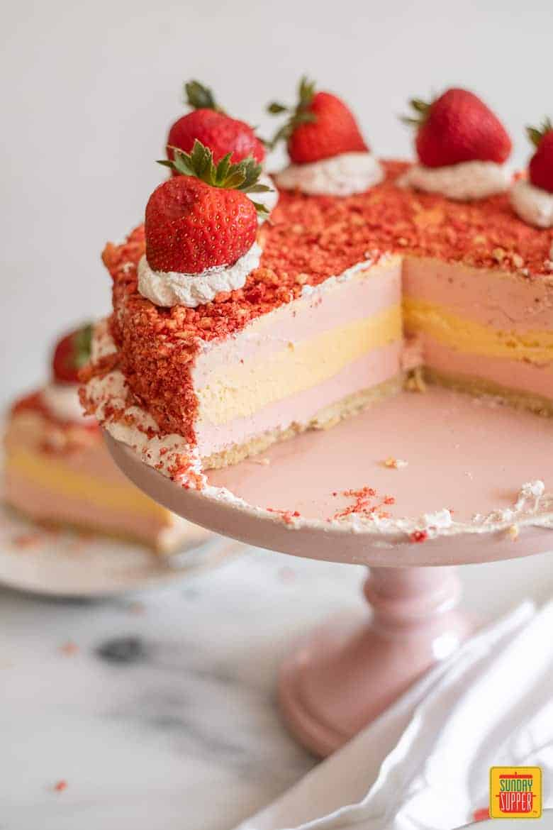 Cake stand of strawberry shortcake cake with two slices missing - Fresh Strawberry Desserts