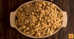 Streusel topping on top of apples in an oval baking dish