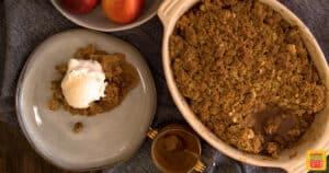 Apple crisp in an oval baking dish next to a slice of apple crisp on a plate with ice cream