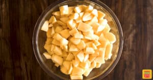 Apples diced in a bowl on a wooden surface