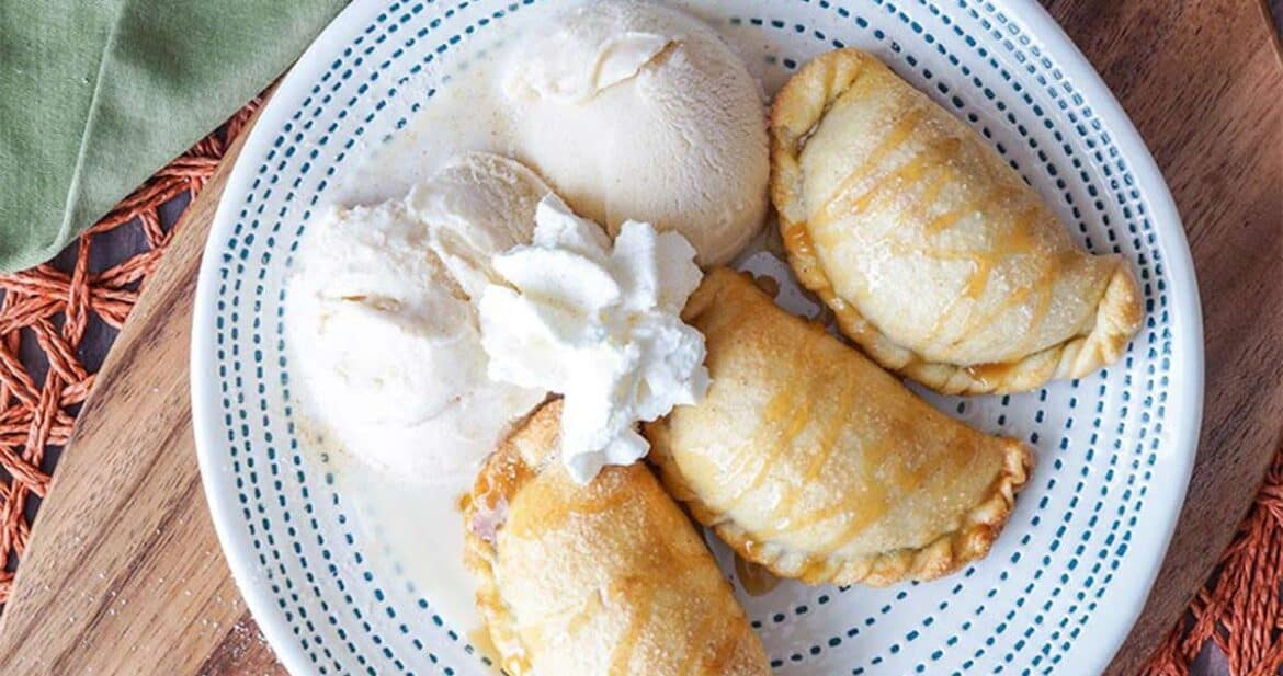 Three Caramel apple empanadas on a white and blue striped plate with ice cream