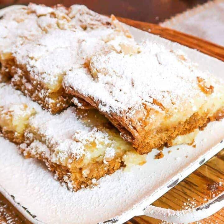 squares of ooey gooey butter cake on a rustic white serving platter