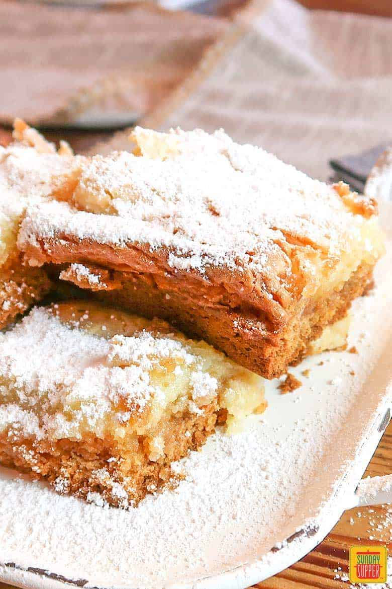 Gooey butter cake bars on a white platter with powdered sugar on top
