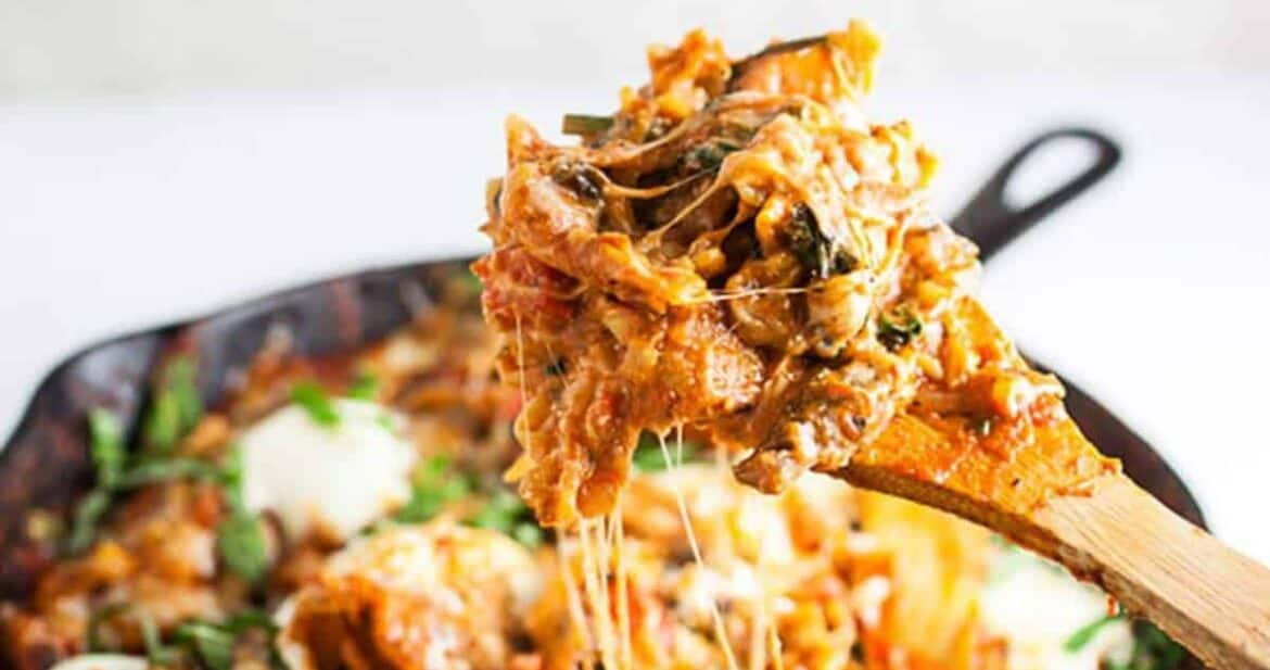 Wooden spoon with skillet lasagna over skillet