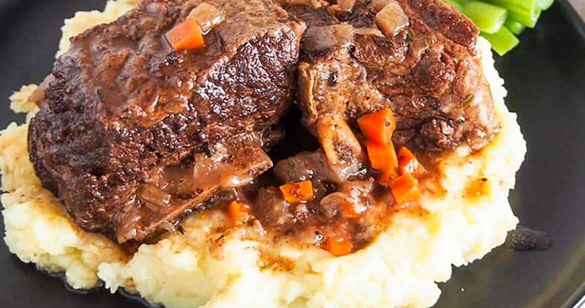 Close up of slow cooker short ribs on a black platter with mashed potatoes and green beans