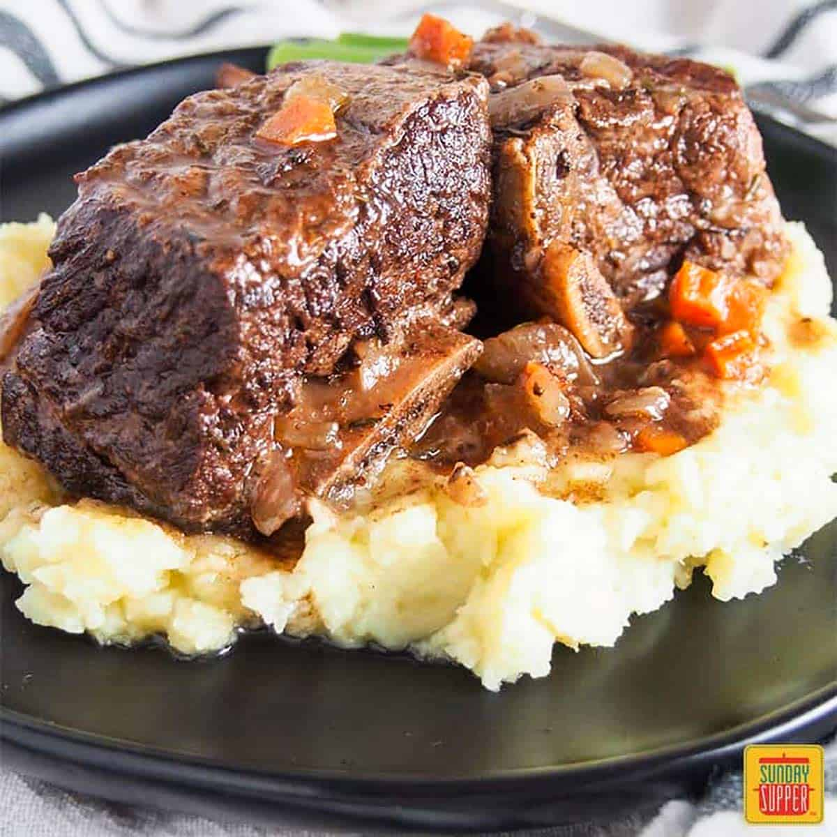 Slow cooker short ribs over a bed of mashed potatoes on a black platter