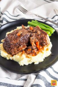 slow cooker short ribs on a black plate with green beans and mashed potatoes