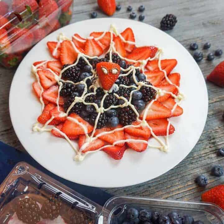 spider-man web berry dessert on white plate surrounded by fresh berries