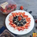 spider-man web berry dessert on white plate with container of wish farms strawberries
