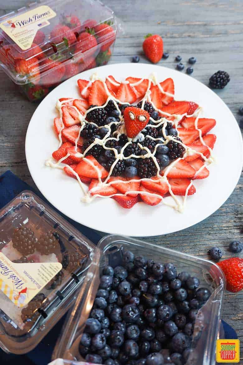 spider-man web berry dessert surrounded by fresh berries ready to enjoy