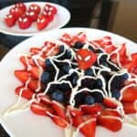 A white plate layered with berries and topped with icing made to look like a spiderweb for Spiderman