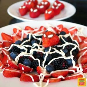 Berries neatly arranged on a neat plate with spiderweb icing and a spiderman face on a strawberry in the center
