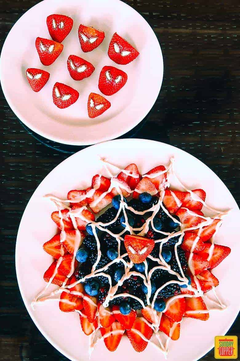 Two plates with spiderman web berry dessert neatly arranged at the center