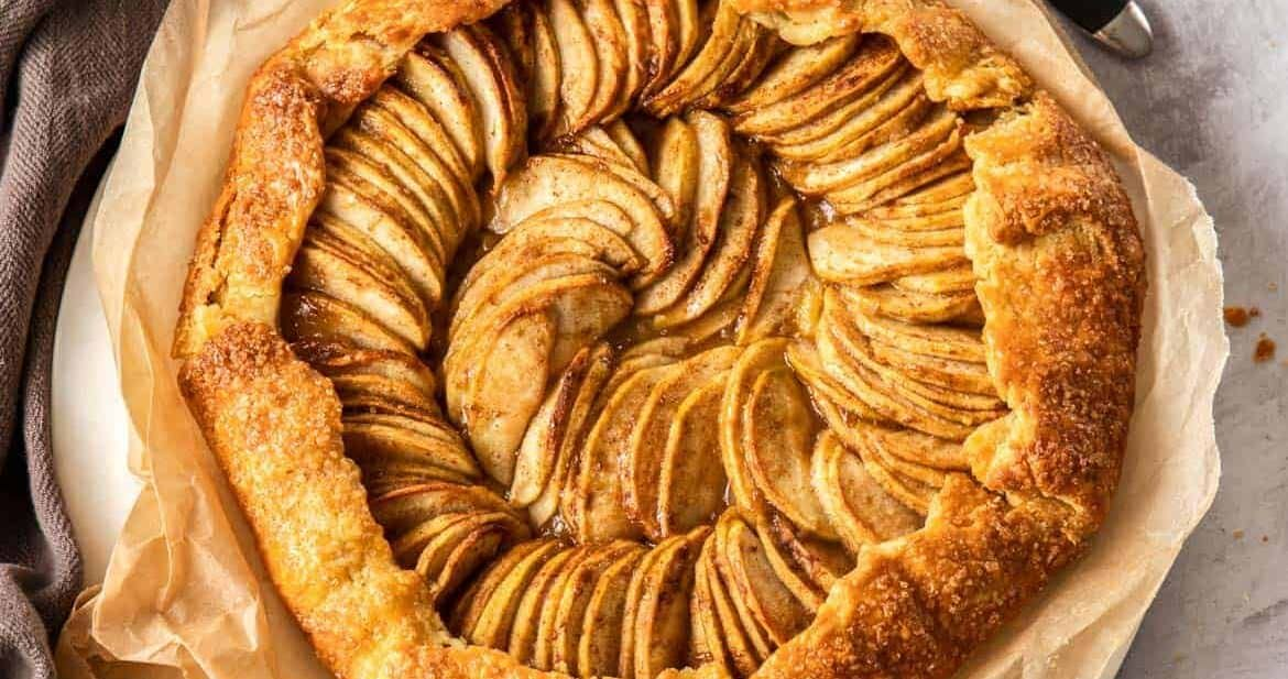Birdseye view of an apple galette on a sheet of baking paper