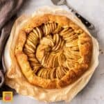 Birdseye view of an apple galette on a sheet of bakign paper. It sits on a concrete background