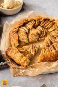 Taking a slice of apple galette on a cake slice. The galette sits on brown baking paper