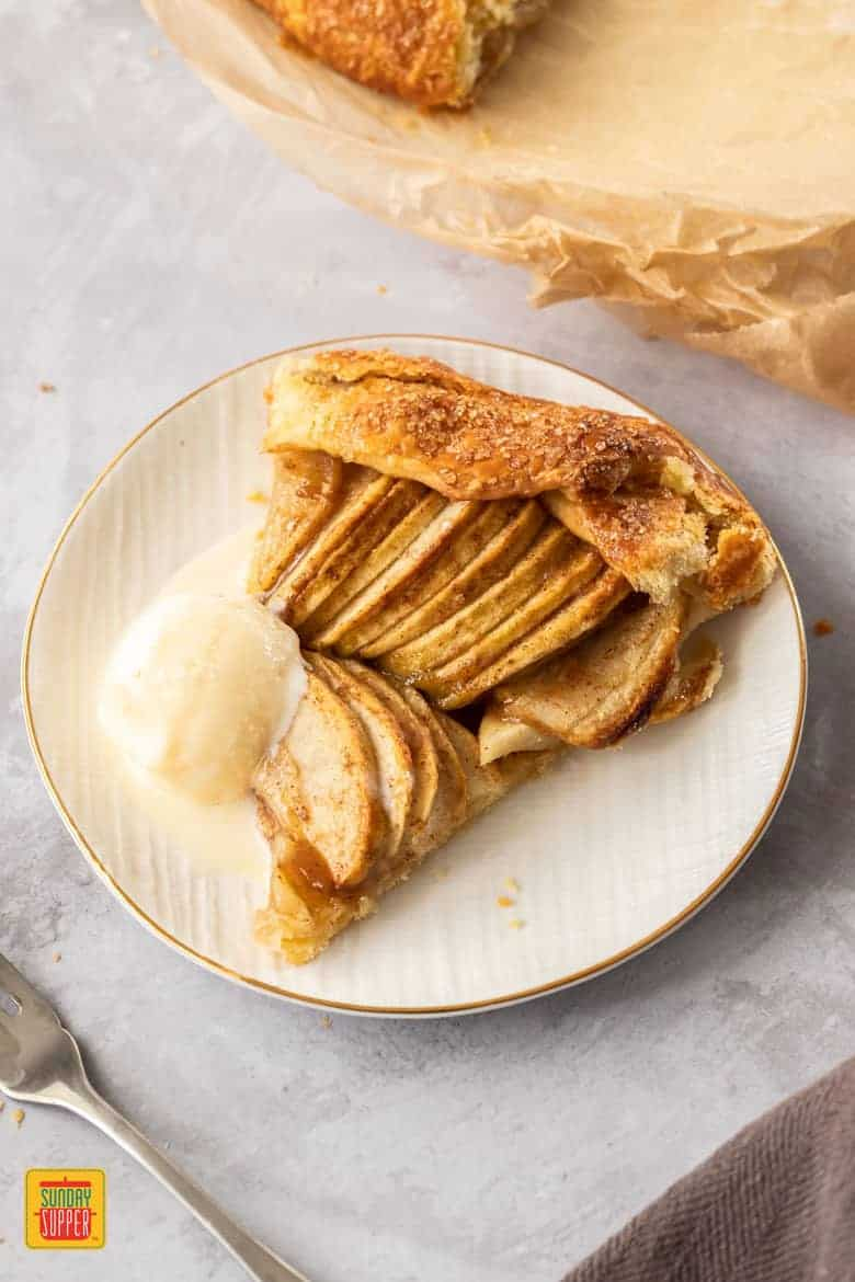 A birdseye view of a slice of apple galette on a white plate. The plate sits on a concrete background