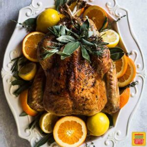A whole garlic butter turkey on a white platter surrounded by fresh citrus and herbs