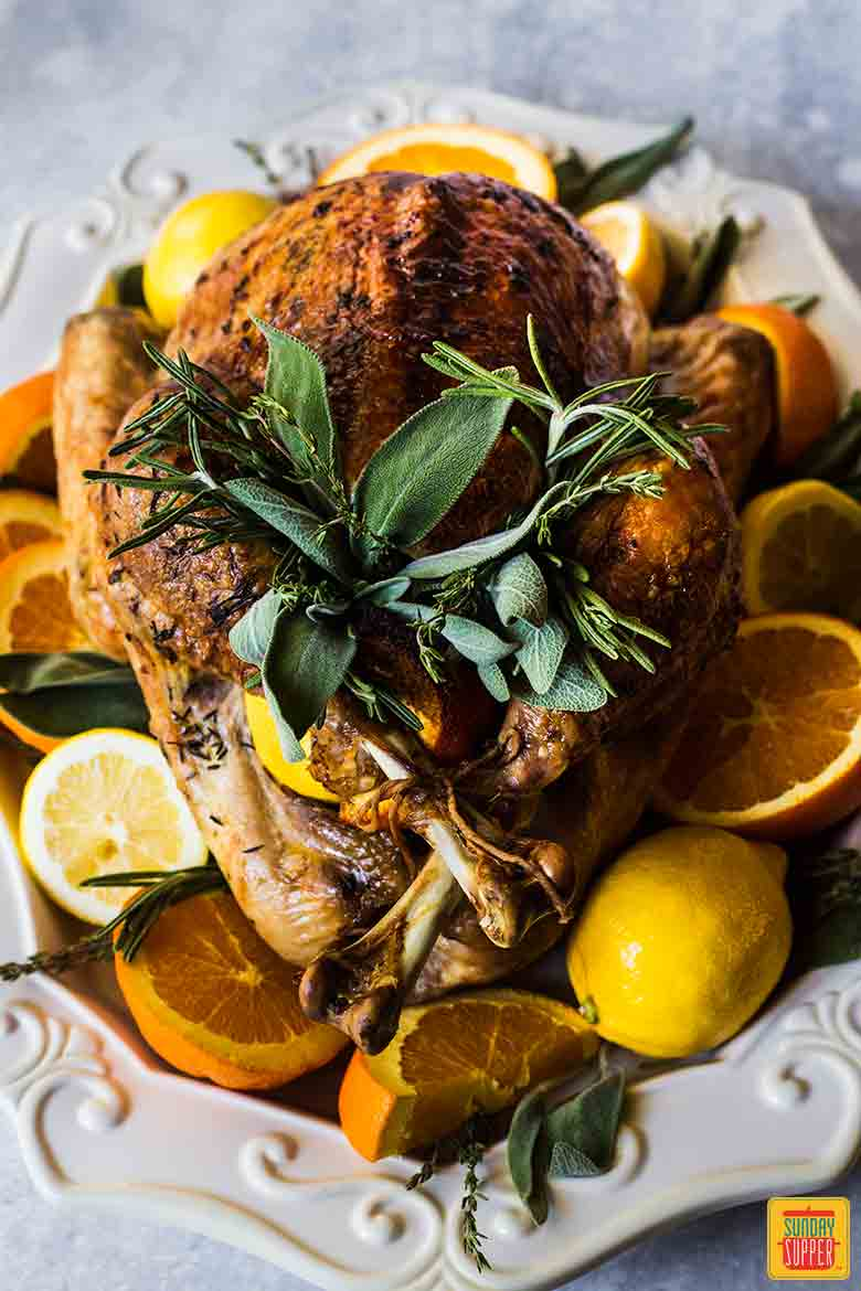 Best Thanksgiving Turkey Recipe on a decorative platter surrounded by citrus