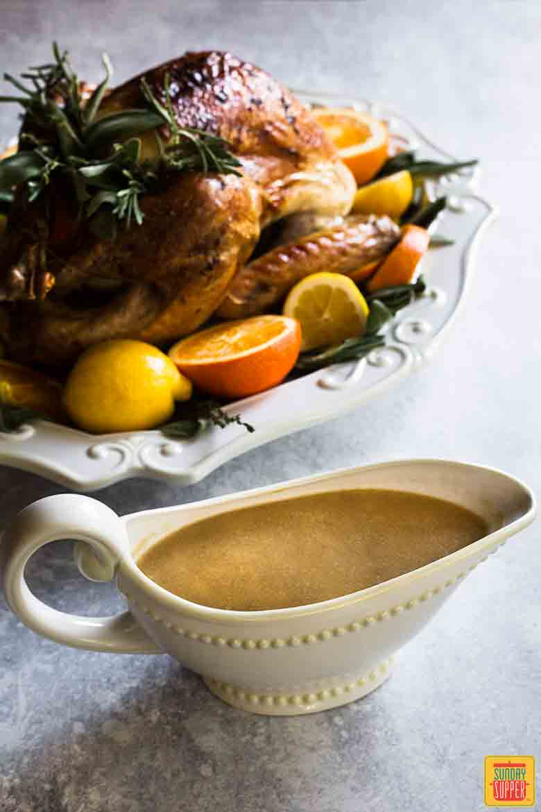 Best Thanksgiving Turkey Recipe on a platter with a gravy boat full of gravy