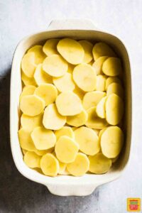 Potatoes layered in dish for Easy Scalloped Potatoes Recipe