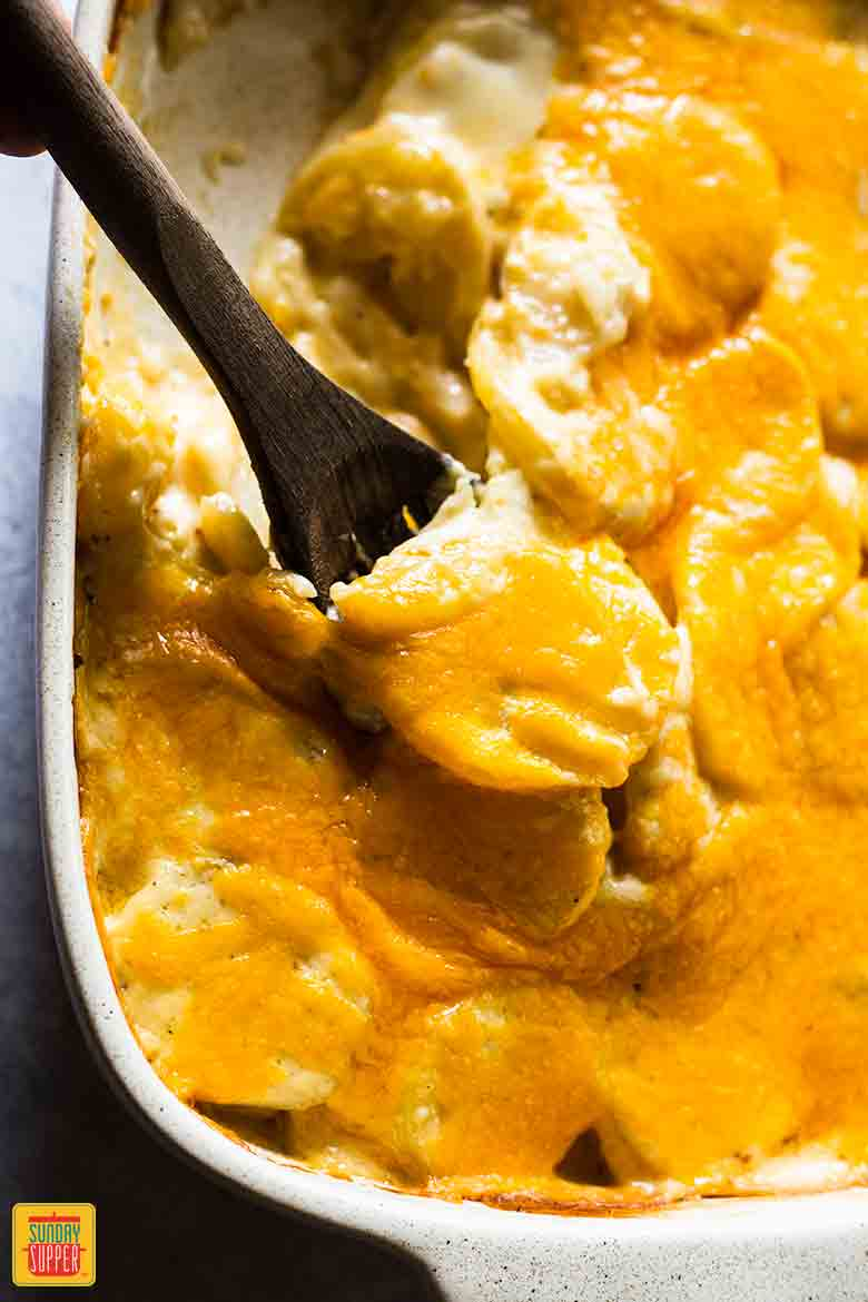 Lifting scalloped potatoes out of the casserole dish with a wooden slotted spoon