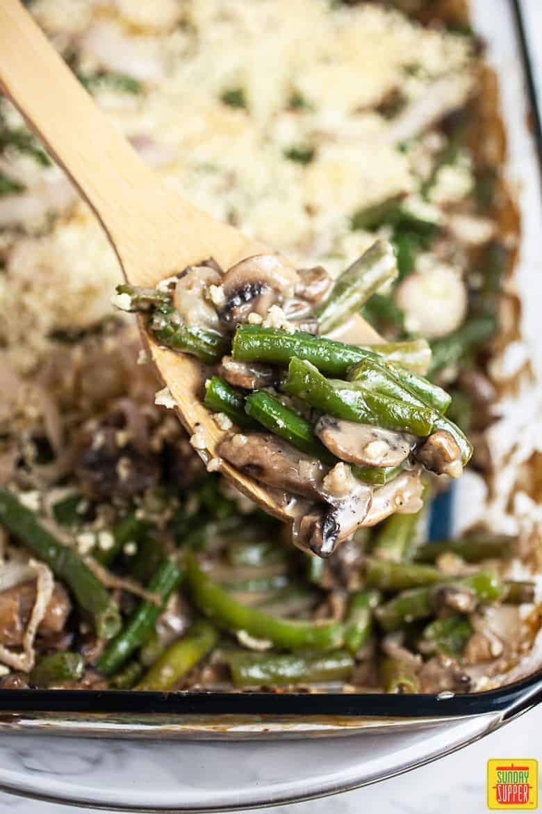 A gluten-free green bean casserole in a glass dish with a wooden serving spoon