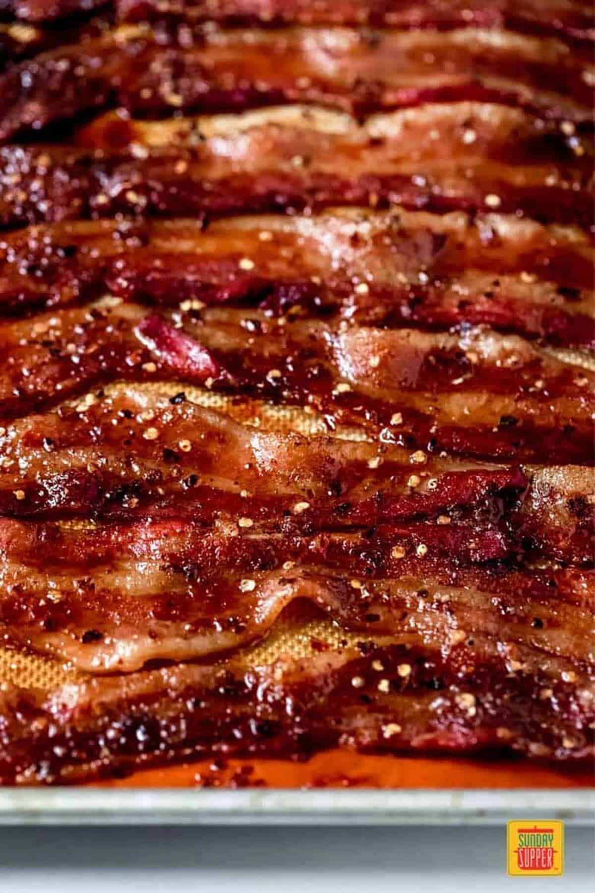 cooked candied bacon on a lined sheet pan