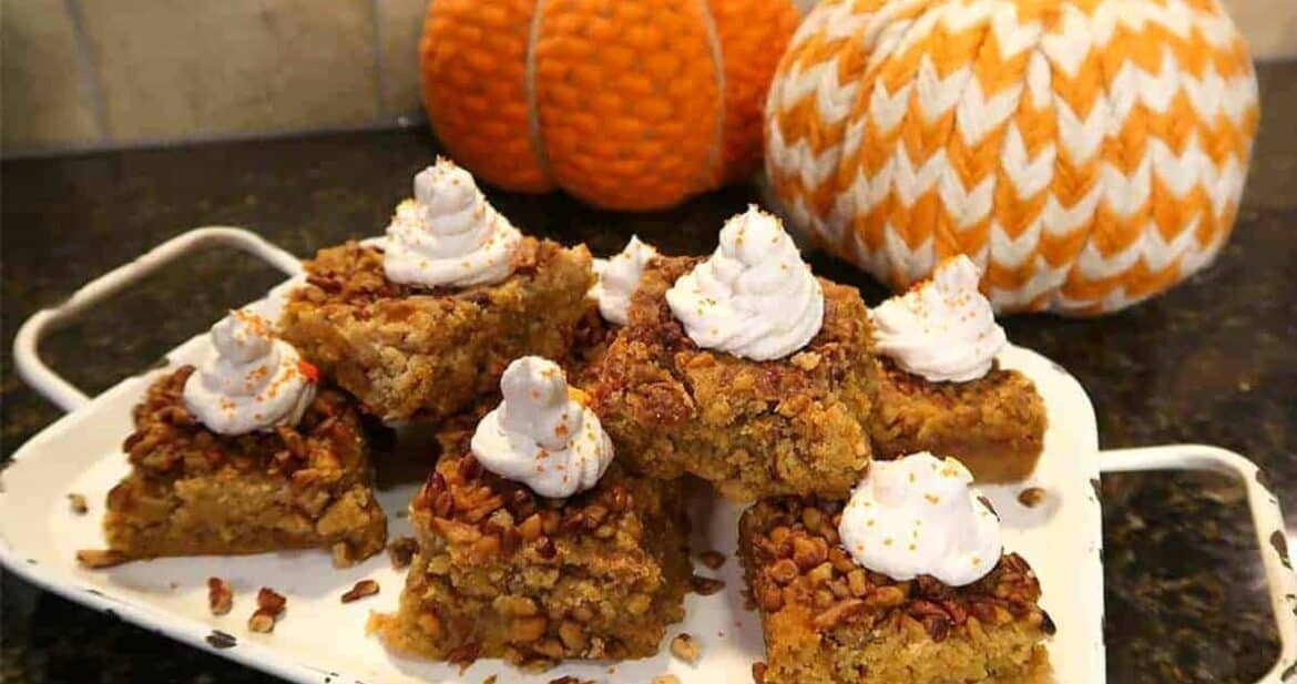 Pumpkin crunch cake bars on a white platter with fabric pumpkins in the background