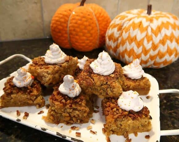 pumpkin crunch cake on a white platter with two decorative pumpkins in background