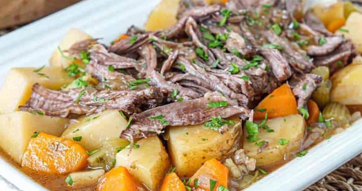 Slow cooker chuck roast with roast potatoes and carrots on a white platter