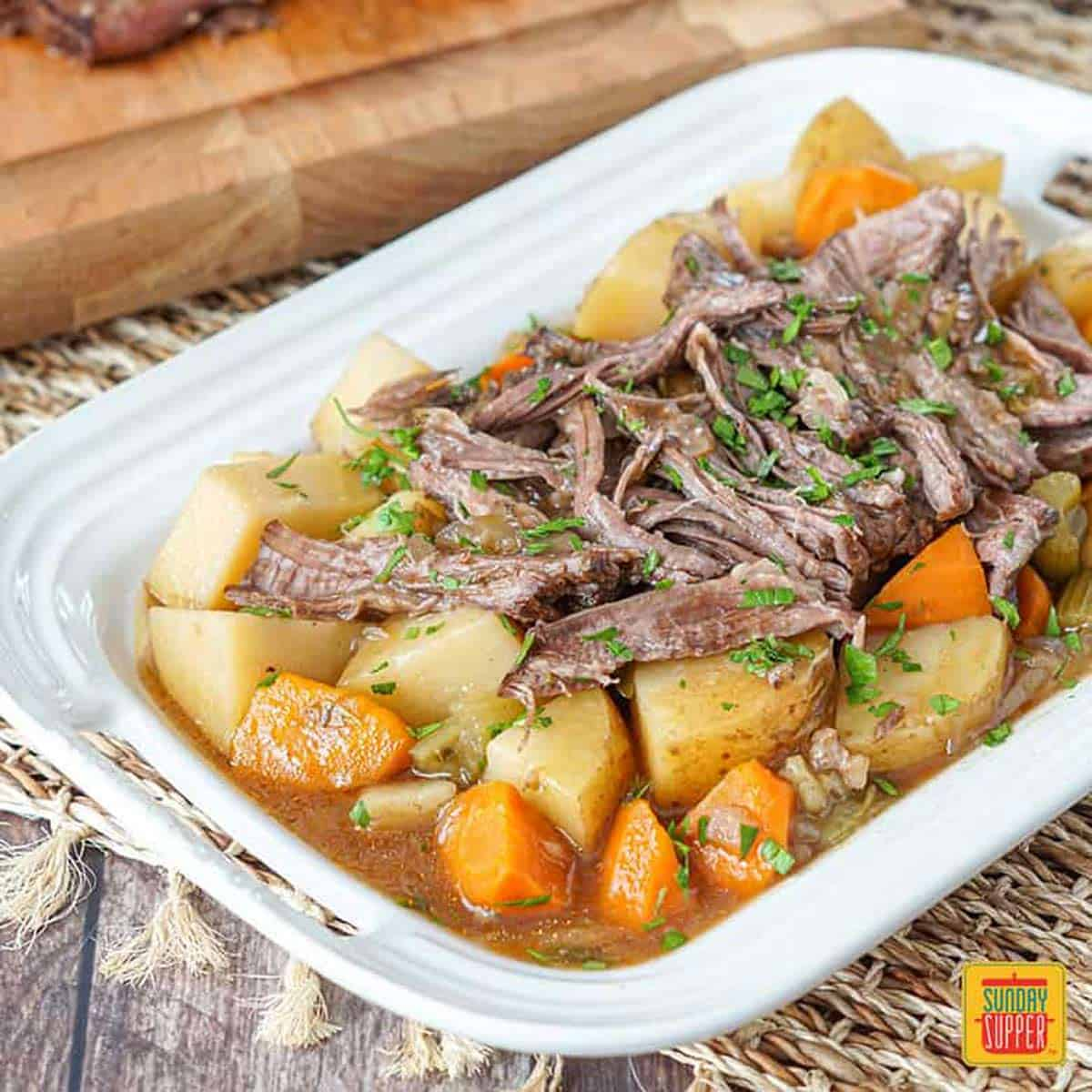 Close up of slow cooker chuck roast on a white platter with potatoes and carrots