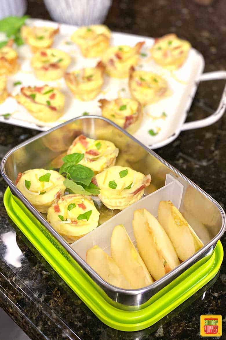 Starbucks egg bites in a bento box with apple slices for an on-the-go breakfast