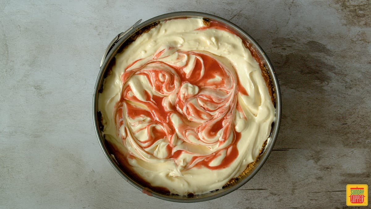 strawberry swirl cheesecake in the springform pan before baking