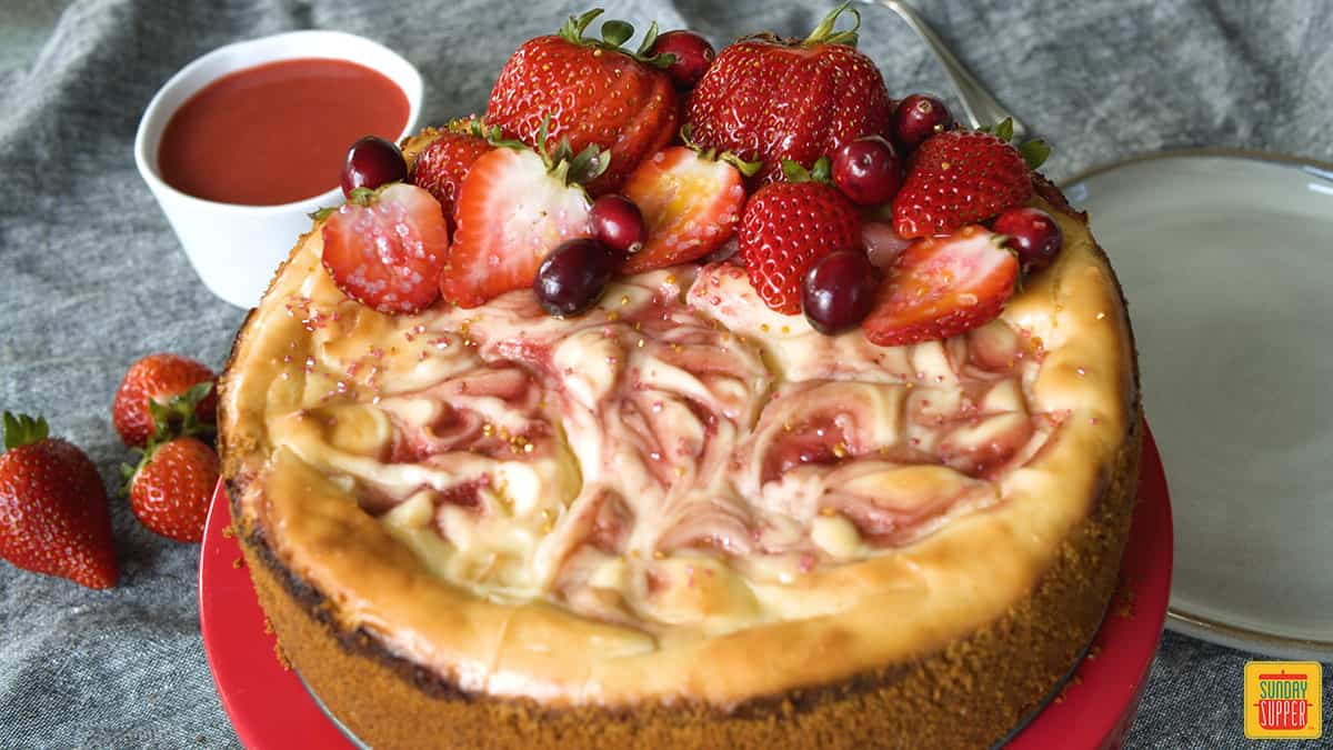 Strawberry swirl cheesecake with fresh berries on top