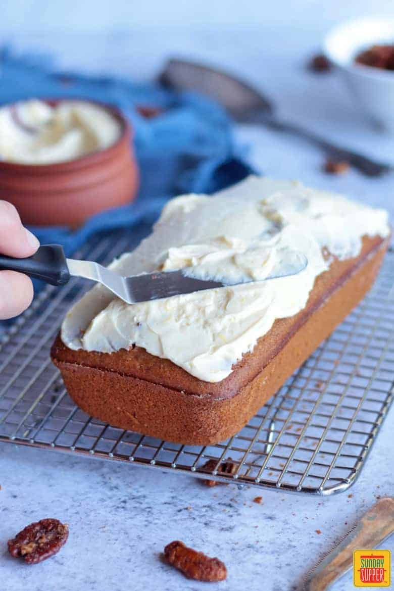 Spreading cream cheese frosting on the cooled gingerbread loaf over a rack