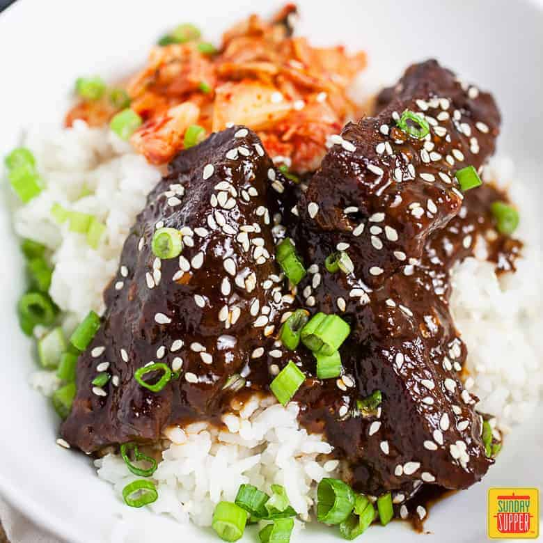 Korean braised short ribs (Galbi Jjim) over a bed of rice and kimchi