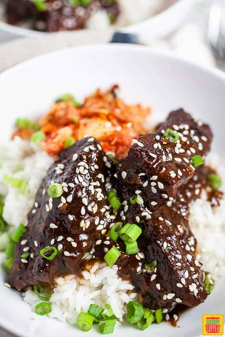 Korean Braised Short Ribs (Galbi Jjim) over rice with kimchi on a white plate