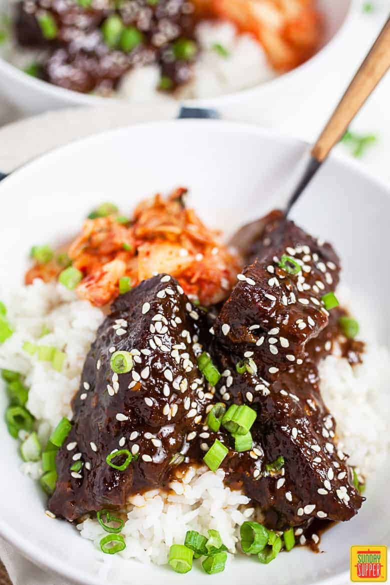 Korean braised short ribs over rice in a white dish