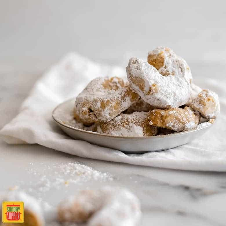 Crescent-shaped Greek wedding cookies in a white dish