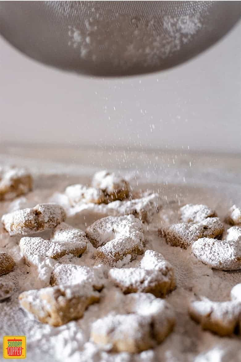 Sprinkling Greek butter cookies with confectioner's sugar
