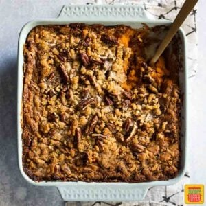 Southern Sweet Potato Casserole in a serving dish with a wooden spoon to dish some out