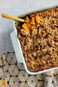 Southern sweet potato casserole in a baking dish with a serving spoon
