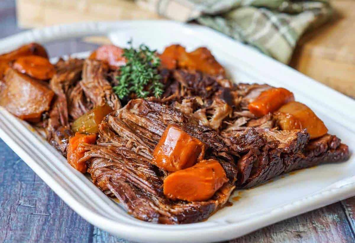Close up of beef chuck roast on a white platter, shredded with carrots and herbs