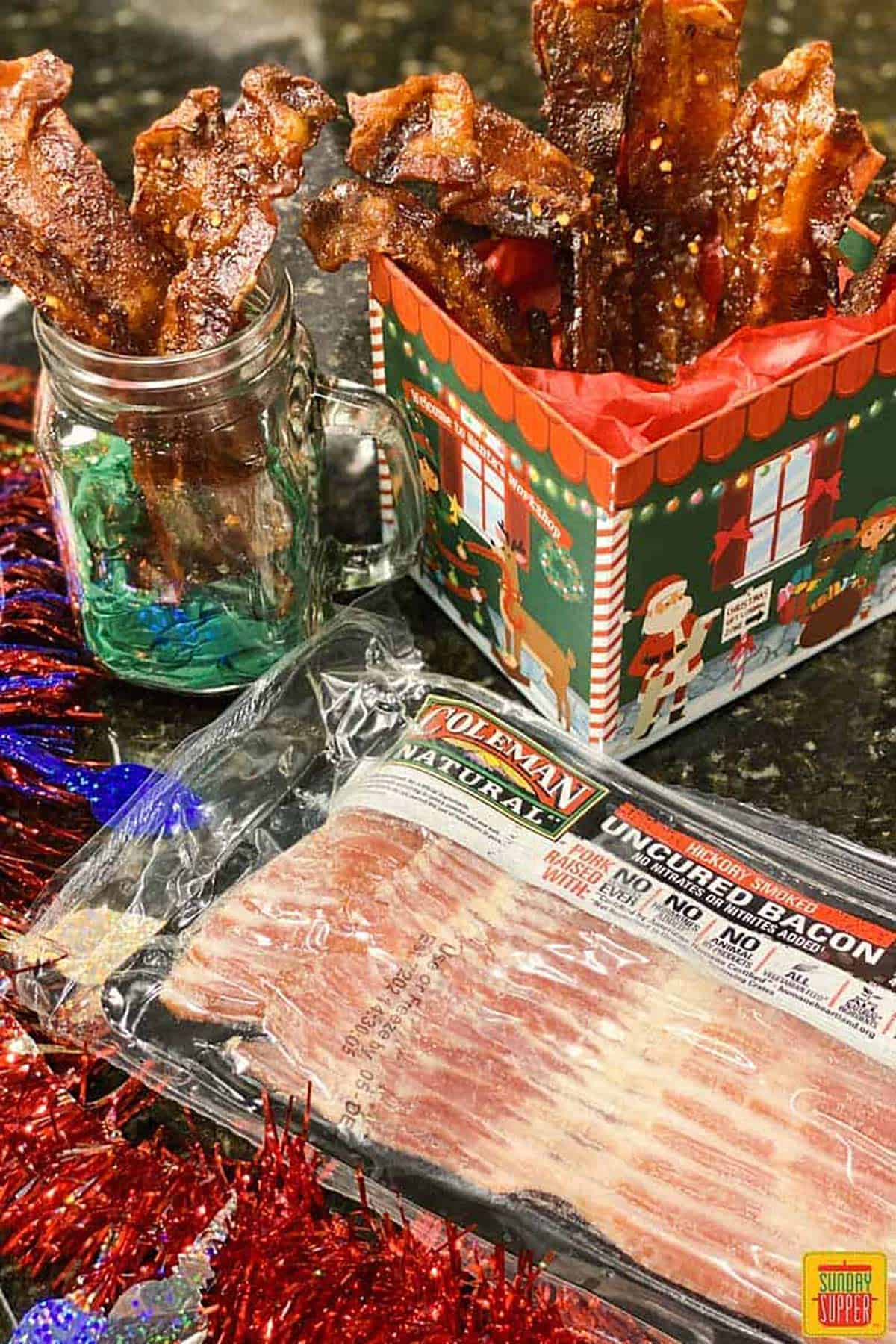 package of bacon with completed candied bacon in a jar and Christmas box